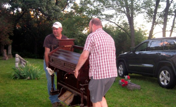 Wally McManaway and Steve Wade deliver an 1865 vintage Estey pump organ to the church at East Richmond Cemetery.