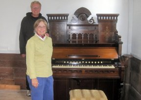 Photo of Georgia Kestol Bauer and Rev. Larry Froemming with a 19th century Estey Pump Organ