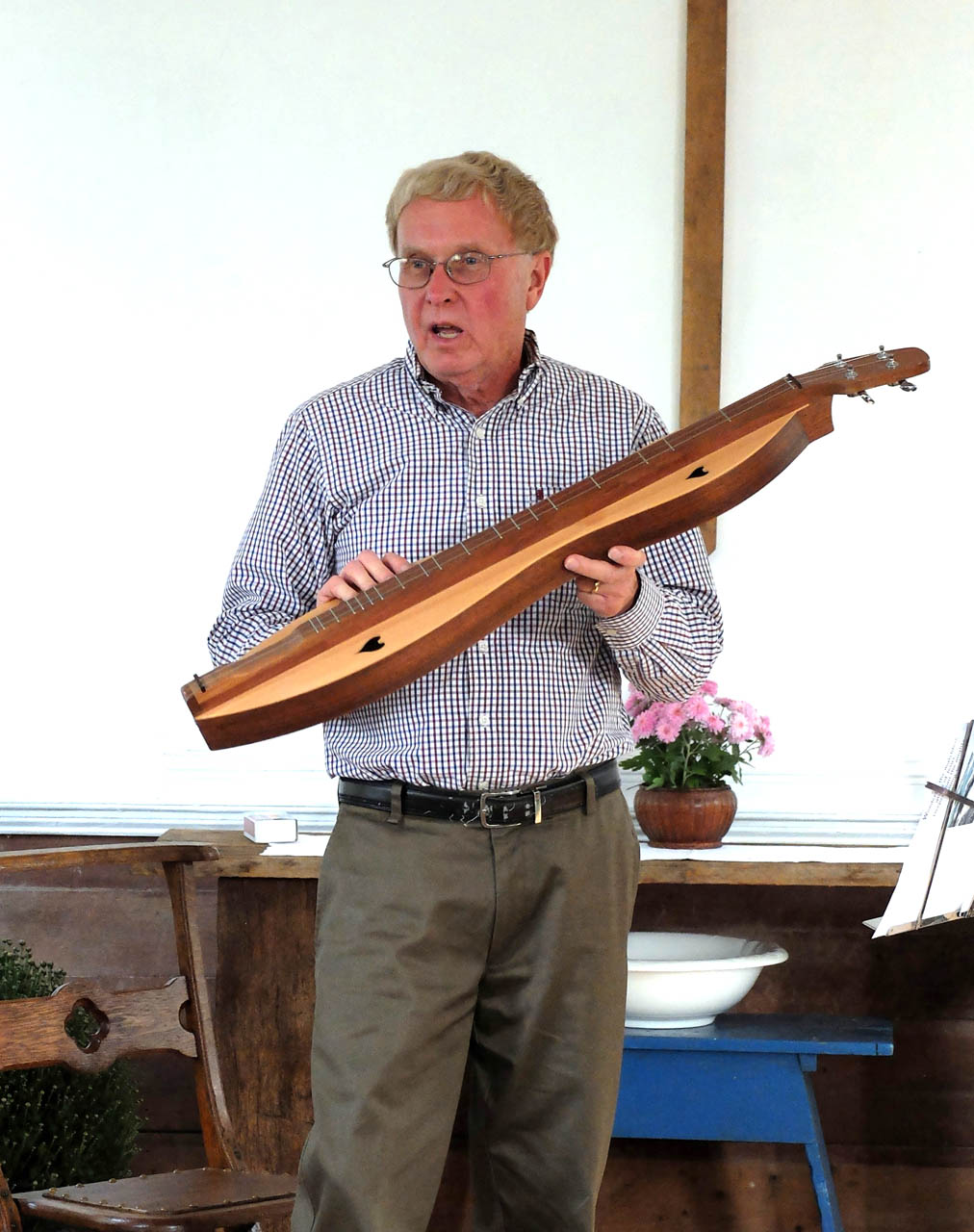 Photo of Rev. Froemming holding a dulcimer